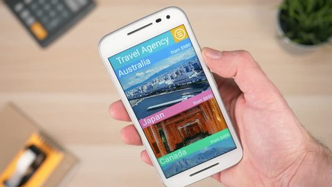 Using a smartphone to check a travel agency app where many deals are showed. Scrolling trough destinations around the world. Shopping for a trip.
