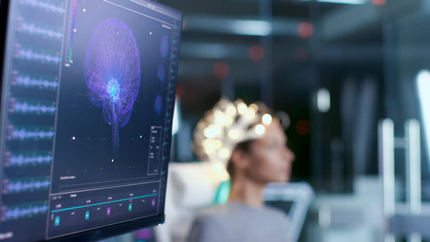Woman Wearing Brainwave Scanning Headset Sits in a Chair In the Modern Brain Study Laboratory/ Neurological Research Center. Monitors Show EEG Reading and Brain Model. Shot on RED EPIC-W 8K Camera.