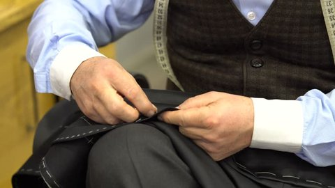 Tailor sewing pants with needle and thread