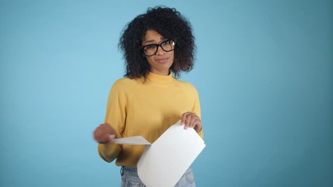 Breaking contract. Furious young african american woman with afro hairstyle tearing up paper with pleasure on blue background. 4k