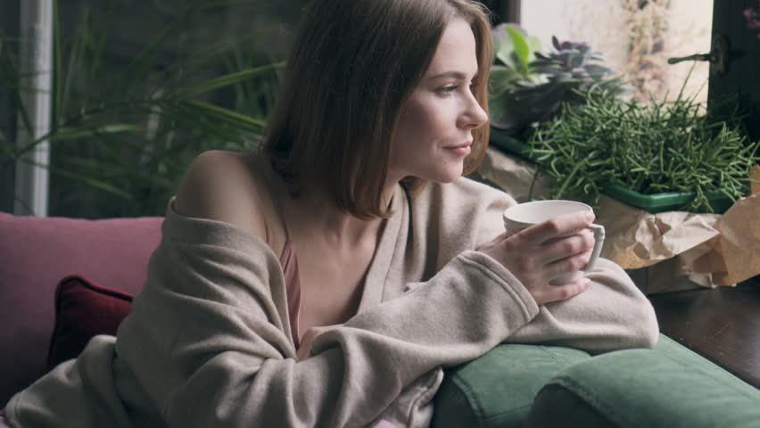 Young woman with cup of coffee getting up with telephone from sofa | Shutterstock HD Video #1007626492