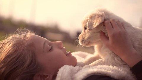 Girl Kid Kissing Hugging Petting Golden Retriever Labrador Puppy Outdoors Close Up Emotional