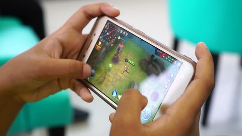 THAILAND, RAYONG - FEB 18, 2018 Teen playing Garena RoV Mobile MOBA game app on smart phone. Garena RoV is most popular of mobile games in the world