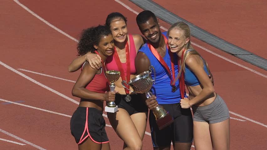 Happy multiethnic winners posing to cameras on sport field, successful team | Shutterstock HD Video #1007644279