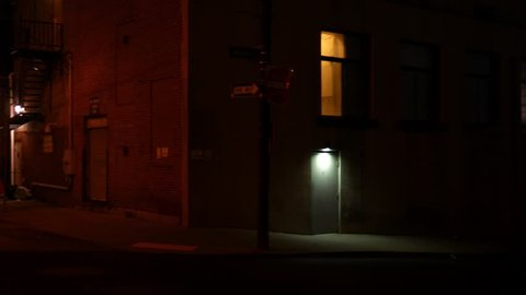Camera pans to creepy alley at night in downtown city