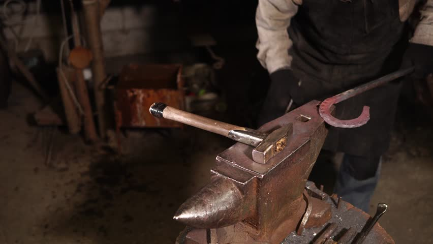 Blacksmiths is forming decor on forged horseshoe. It is lying over big incus near hammer, one master is fixing gavel on edge and second is hitting
