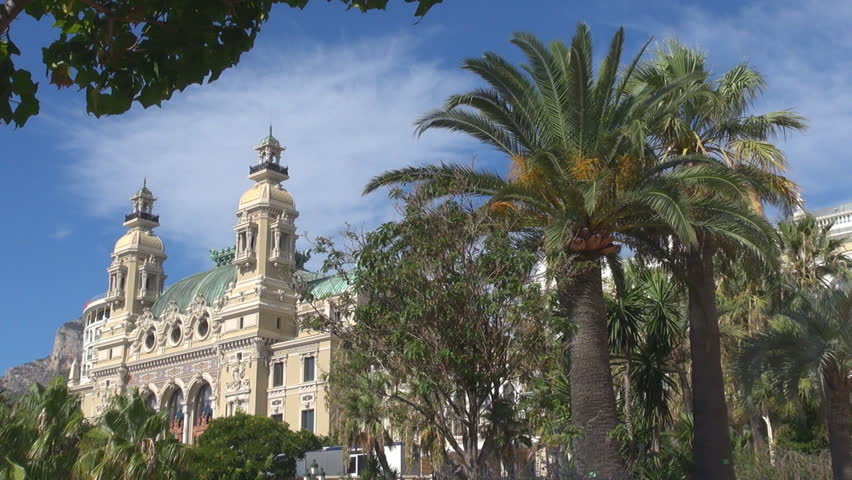 Beautiful Casino Palace gambling building in Monte Carol, palm tree in windy day