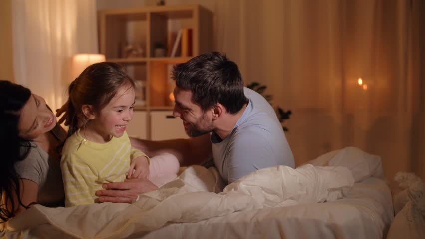 Family and people concept - happy mother, father and little daughter having fun in bed at home