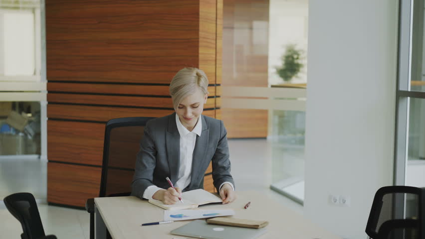 Two business colleagues discussing reports in modern office. Businesswoman sitting at the table talking his male partner | Shutterstock HD Video #1007692129