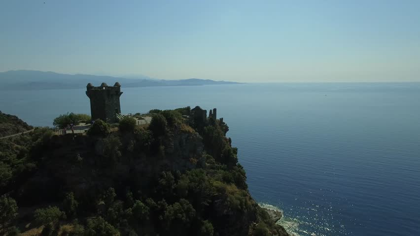 Aerial view of Tower of Nonza on the top of a cliff, in front of beautiful turquoise sea of Corsica