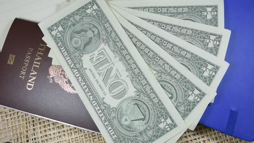 People are counting the dollar of America and the Thai passport is placed on the table,The use of dollars for cheap travel abroad,The use of dollars for foreign purchases.    Shutterstock HD Video #1007708167