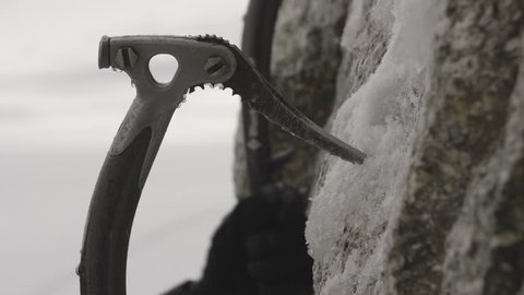 Close up shot of an ice axes hooking onto the rock as the climber moves upwards.
