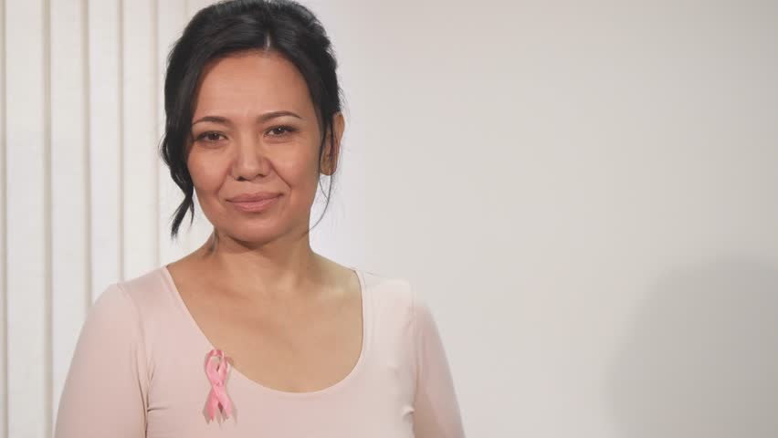 Happy beautiful mature Asian woman wearing pink ribbon breast cancer awareness symbol smiling to the camera copyspace positivity vitality joy wellbeing health prevention patient.