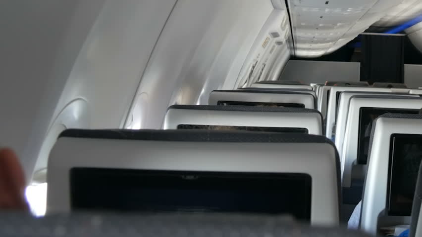 Passengers in comfortable seats of aircraft with the screens in chairs   Shutterstock HD Video #1007712721