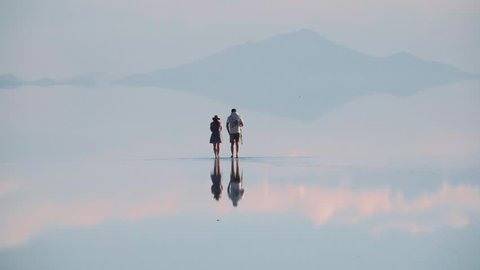 Tourist walking on the Uyuni salt flats in the rain season, reflection of the sunset and the people walking, Bolivia.
