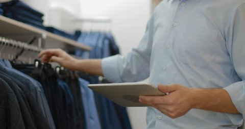 A young, promising manager works in a clothing store. tracking shot. in slow motion