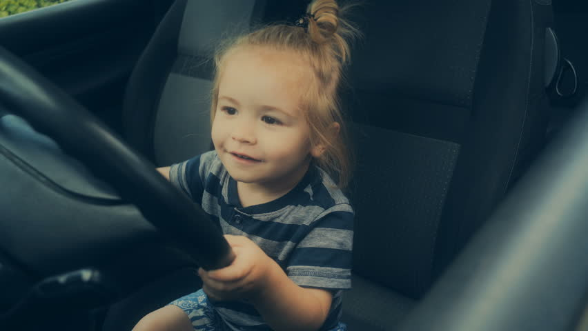 Steering wheel, driving school, driving as a hobby. Boy with long hair likes cars. Cute kid in a daddy car in the front seat. Safety at the wheel. Passenger car for children. Baby on board