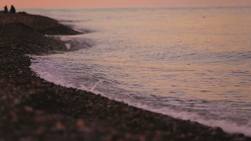Gentle ocean waves hitting pebble beach shoreline, tranquil sea water seascape