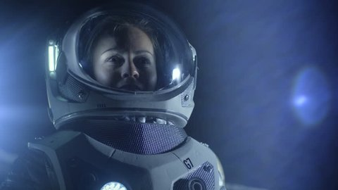 Portrait of the Beautiful Female Astronaut on the Alien Planet Looking around in Wonder. In the Background Living Quarters. Space Travel, Exploration. Shot on RED EPIC-W 8K Helium Cinema Camera.