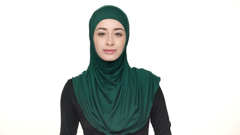 Portrait of young religious woman in traditional headscarf showing index finger on camera meaning hey you, over white background. Concept of emotions