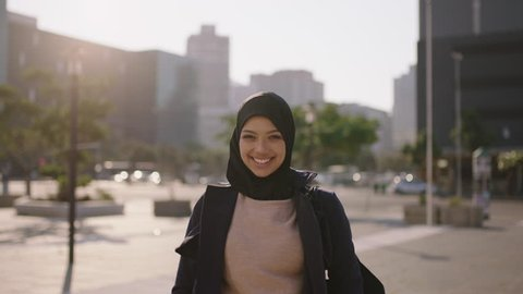 portrait of young happy muslim business woman smiling looking at camera confident wearing hijab headscarf in windy city enjoying urban lifestyle