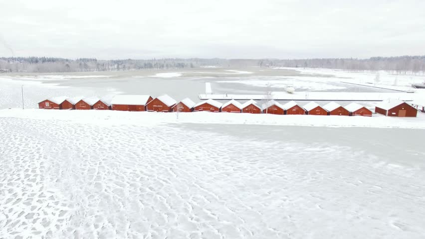 Flying over wooden red boathouses towards a frozen river mouth at a frozen lake in Kerimaki, Finland. Aerial time-lapse.