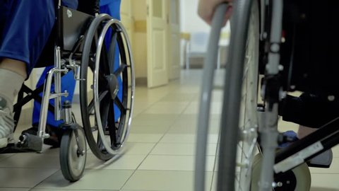 Young guy, a disabled person with a lesion of the spinal cord and legs, multiple sclerosis, moves through the hospital corridor in a wheelchair.