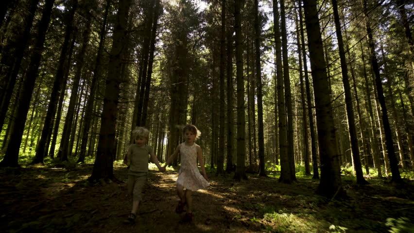Two kids running through woods in Denmark | Shutterstock HD Video #1007786293