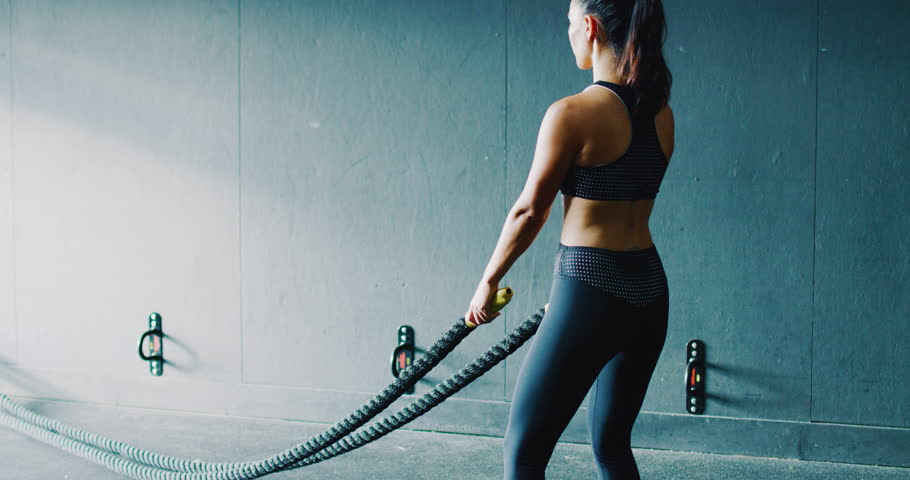 Beautiful athletic woman exercising with battle ropes in the gym | Shutterstock HD Video #1007803513