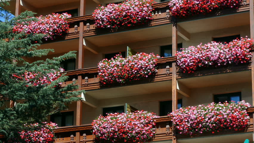 """Beautiful building in spring. Balconies with planters full of flowers, in the town of """"La Massana"""" (Andorra), with camera movement:Panning left."""