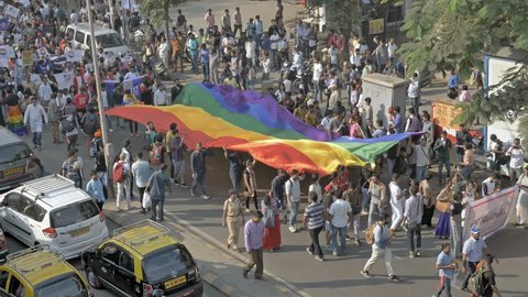 Crowd of people carrying large LGBT pride flag or rainbow flag walking on the  road during LGBT or gay pride parade, Mumbai, India (2018)