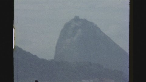 RIO DE JANEIRO, BRAZIL, MARCH 1976. Zoom Out Shot Of The Sugarloaf, Or Pao De Acucar And Pan Over The Copacabana Beach And Seaside Street Traffic From A High Building.