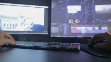 Video editing process in timelapse, table with 2 monitors and black keyboard in dark room
