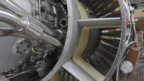 The side view of structure of the aircraft engine. There are lots of pipes, pumps, compressors, gears, pulleys, blades, valves, hydraulic and servo drives and other elements