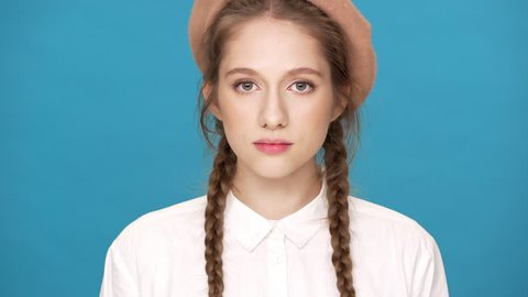 Portrait closeup of adorable woman 20s wearing beret and two braids hairstyle posing on camera with lovely smile, isolated over blue background