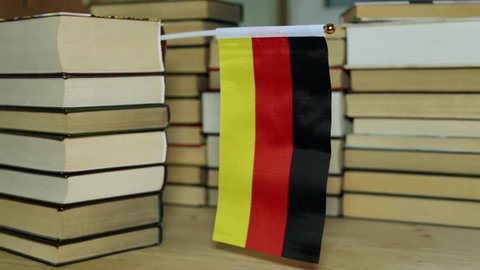 German flag with books. Flag of Germany and paper books.
