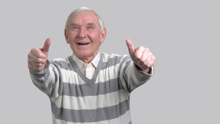 Happy grandfather with two thumbs up. Cheerful eldery man giving thumbs up sign on grey background. Gesture of success and happiness.
