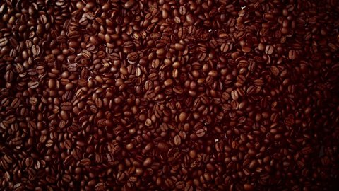 top view of coffebeans falling from camera down to coffe beans background slowmotion