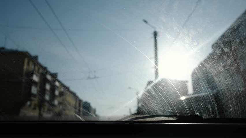 View from the car to the city. Focus on the dirty windshield. The car is in motion. #1007893153
