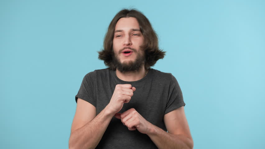 Portrait of caucasian happy man 20s wearing casual gray t-shirt and necklace dancing and singing in studio, over blue background. Concept of emotions