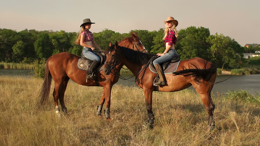 Two Girls Are Sit Horses That Have Touched Their Heads Against The Background Of Lake