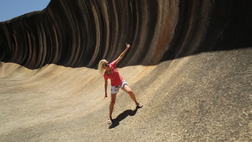 Young woman enjoying surfing on the Wave Rock, a natural rock formation shaped like a high breaking ocean wave, in Hyden, Western Australia. Happy funny girl surfing in Australian outback.
