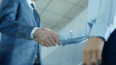 Low Angle Close-up Shot of the Businessman with Businesswoman Shaking Hands with Emphasis on Handshake. Shot on RED EPIC-W 8K Helium Cinema Camera.