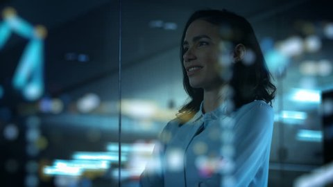 Beautiful Female CEO in Her Office Looks out of the Window on a Big City at Night. Strong Independent Woman with Big Accomplishments Behind and Ahead of Her. Shot on RED EPIC-W 8K Helium Cinema Camera
