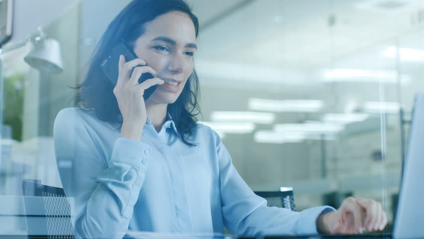Beautiful Female Office Worker Makes a Client Call and Talks on the Mobile Phone while Sitting at Her Working Desk. Shot on RED EPIC-W 8K Helium Cinema Camera.
