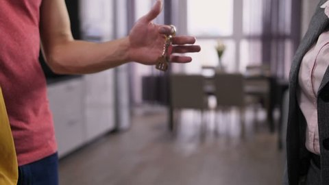 Close-up male hands clasping new home keys and female owner's handshake with real-estate agent. Midsection of happy couple getting new apartment keys from female realtor. Slow motion