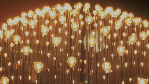 Hundreds of edison vintage retro lightbulbs brighten up darkness in different order and rhythm, perform as symbols of ideas, startup and creativity, new business beginnings