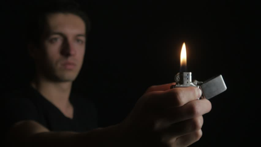 Close up Man opening and the burning of iron Zippo lighter on a black background