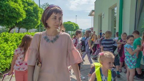 GRIZE/CELJE, SLOVENIA - 10. JUNE 2017 Mom and daughter comes to school hand-in-hand. It's her daughter's first day at school.
