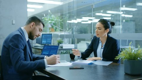 Businesswoman and Businessman Have Conversation. Draw up a Contract, Filling Papers in Conference Room. In the Background Modern Bright Office with Glass Walls. Shot on RED EPIC-W 8K Helium Camera.